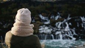 Opinião traseira a mulher bonita nova que está perto da cachoeira de Barnafoss em Islândia e que aprecia a paisagem cênico video estoque