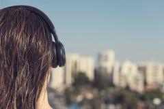 Opinião traseira a mulher com cabelo molhado no fones de ouvido no balcão de seu apartamento contra o contexto da estância turíst foto de stock royalty free