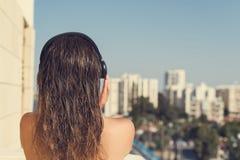 Opinião traseira a mulher com cabelo molhado no fones de ouvido no balcão de seu apartamento contra o contexto da estância turíst imagem de stock