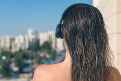 Opinião traseira a mulher com cabelo molhado no fones de ouvido no balcão de seu apartamento contra o contexto da estância turíst imagens de stock