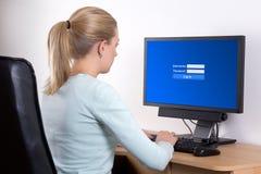 Opinião traseira a mulher com computador pessoal usando o email ou o social fotos de stock