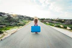 Opinião traseira a mulher com mala de viagem azul em uma estrada imagens de stock royalty free
