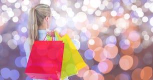 Opinião traseira a mulher com os multi sacos de compras coloridos sobre o bokeh Fotos de Stock Royalty Free