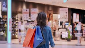 Opinião traseira a mulher com os sacos de compras no shopping vídeos de arquivo