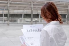 Opinião traseira a mulher de negócio asiática nova segura que analisa cartas ou documento no escritório exterior imagens de stock