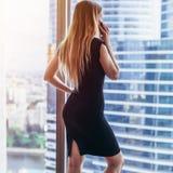 Opinião traseira a mulher de negócios bem sucedida que tem a conversa telefônica que olha para fora a janela com opinião da arqui fotografia de stock