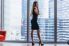 Opinião traseira a mulher de negócios bem sucedida que tem a conversa telefônica que olha para fora a janela com opinião da arqui imagem de stock