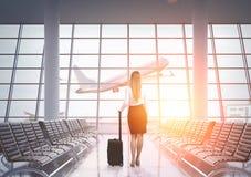 Opinião traseira a mulher de negócios no aeroporto, tonificada Imagem de Stock Royalty Free