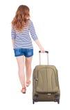 Opinião traseira a mulher de passeio com mala de viagem Fotos de Stock Royalty Free