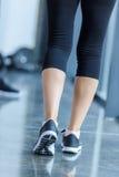 Opinião traseira a mulher desportiva em estar do sportswear e das sapatilhas foto de stock