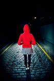Opinião traseira a mulher em Hood On Street At Night vermelho Imagens de Stock