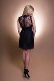 Opinião traseira a mulher loura bonita nova no vestido sobre o bege imagens de stock royalty free