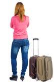 Opinião traseira a mulher loura com a mala de viagem que olha acima Fotos de Stock Royalty Free