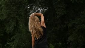 Opinião traseira a mulher loura no fundo da natureza Poses bonitas da menina com cabelo do voo Movimento lento vídeos de arquivo