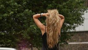 Opinião traseira a mulher loura no fundo da natureza Poses bonitas da menina com cabelo do voo Movimento lento video estoque