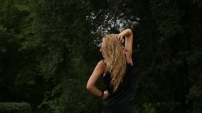Opinião traseira a mulher loura no fundo da natureza Poses bonitas da menina com cabelo do voo Movimento lento filme