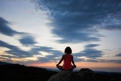 A opinião traseira a mulher magro nova que senta-se na rocha grande na pose dos lótus da ioga na árvore verde cobre o céu da noit fotos de stock royalty free