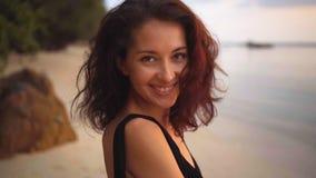 A opinião traseira a mulher moreno encaracolado de cabelos compridos atrativa gerencie para a câmera e dá um sorriso bonito filme