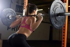 Opinião traseira a mulher no Gym que levanta peso no Barbell imagem de stock royalty free
