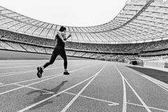 Opinião traseira a mulher nova da aptidão no sportswear que corre no estádio da pista de atletismo imagem de stock royalty free
