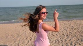 A opinião traseira a mulher que anda na praia à água do mar, gerencie e convida para segui-la no curso das férias Senhora com mag vídeos de arquivo
