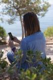 Opinião traseira a mulher que guarda o telefone Foto de Stock