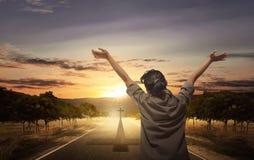 Opinião traseira a mulher que levanta a mão com palma aberta ao rezar Foto de Stock