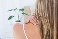 Opinião traseira a mulher que obtém a dor de pescoço fotografia de stock royalty free