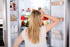 Opinião traseira a mulher que olha no refrigerador fotografia de stock