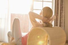 Opinião traseira a mulher que relaxa na cadeira em casa imagem de stock royalty free