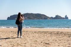 Opinião traseira a mulher que toma imagens com a câmera de DSLR das ilhas da praia - ilhas de Medes fotografia de stock