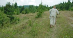 A opinião traseira o ancião na roupa velha está andando ao longo das montanhas com a ajuda de seu bastão filme
