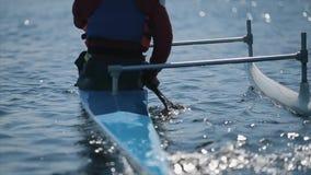 Opinião traseira o atleta deficiente que usa a pá em uma canoa Enfileiramento, canoeing, remando Treinamento kayaking esporte par video estoque