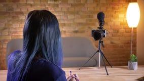Opinião traseira o blogger video fêmea caucasiano atrativo novo que fala na câmera ao fluir viva e ao gesticular filme