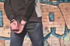 Opinião traseira o delinquente prendido e algemado contra a GR foto de stock