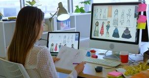 Opinião traseira o desenhador de moda fêmea caucasiano que trabalha no computador na mesa no escritório 4k video estoque