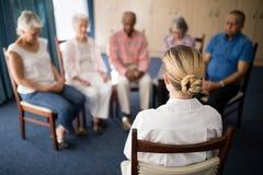 Opinião traseira o doutor fêmea que medita com povos superiores imagens de stock