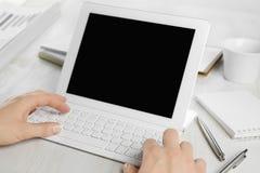 A opinião traseira o empregado entrega o trabalho no teclado de tablet pc fotos de stock royalty free