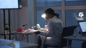 Opinião traseira o engenheiro eletrónico fêmea que verifica o cartão-matriz com o verificador do multímetro video estoque