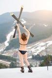 A opinião traseira o esquiador fêmea 'sexy' irreconhecível está estando na inclinação e está guardando esquis acima da cabeça imagem de stock royalty free