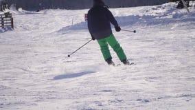 Opinião traseira o esquiador profissional que cinzela abaixo da inclinação nevado vídeos de arquivo