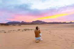Opinião traseira o fotógrafo fêmea do turista que toma a imagem do cenário de nivelamento bonito do por do sol no deserto de Jord foto de stock