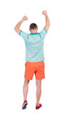 Opinião traseira o homem alegre que comemora as mãos da vitória acima Fotos de Stock Royalty Free
