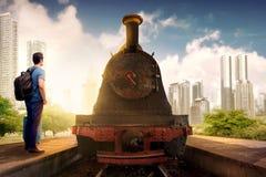 Opinião traseira o homem asiático com posição do saco e da trouxa da mala de viagem e espera de um trem na estação fotos de stock royalty free