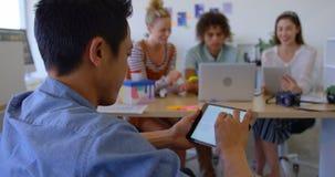 Opinião traseira o homem asiático novo que trabalha na tabuleta digital no escritório moderno 4k vídeos de arquivo