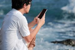 Opinião traseira o homem asiático novo que usa o telefone esperto móvel na costa de mar Internet do conceito das coisas fotografia de stock