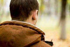 Opinião traseira o homem com os fones de ouvido que guardam o telefone esperto móvel imagem de stock royalty free