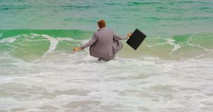 Opinião traseira o homem de negócios caucasiano que anda com a pasta no mar na praia 4k vídeos de arquivo