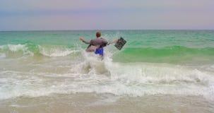 Opinião traseira o homem de negócios caucasiano que corre com a pasta no mar na praia 4k video estoque