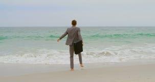Opinião traseira o homem de negócios caucasiano que salta com a pasta na praia 4k video estoque